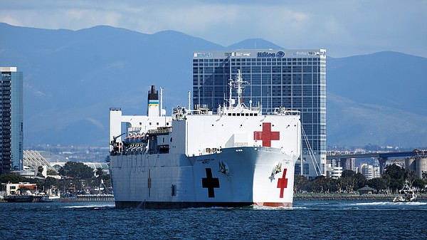 Navy medical and support personnel staff the USNS Mercy, ...