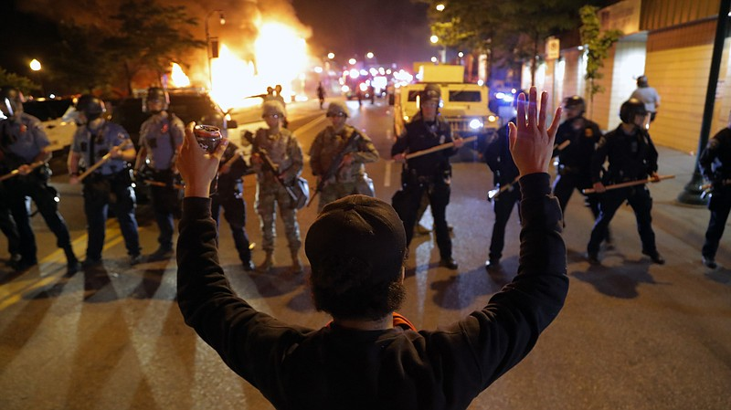 A man raises his hands as police line up across the street during protests Fr...