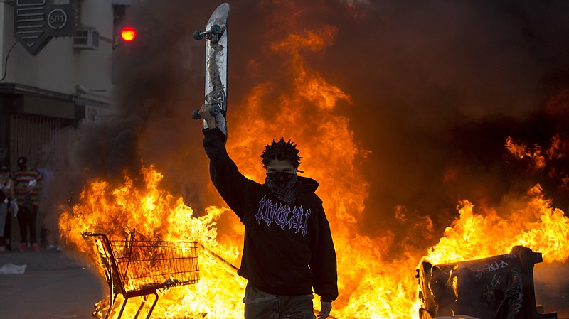 A protester holds a skateboard in front of a fire in Los Angeles, Saturday, M...