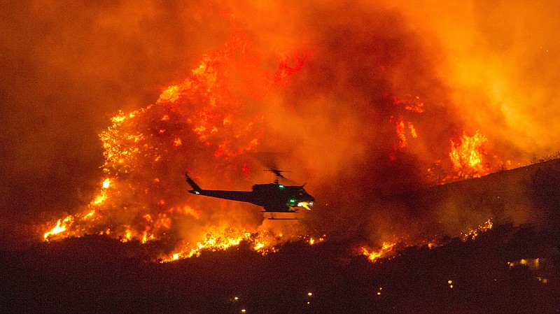 A helicopter prepares to drop water at a wildfire in Yucaipa, Calif., on Sept...