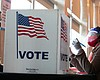A poll worker helps K. Maki (left) fill out a p...