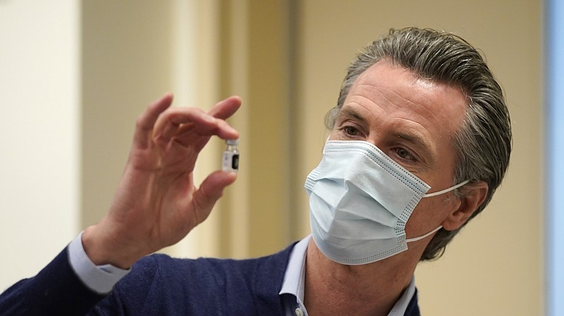 California Gov. Gavin Newsom holds up a vial of the Pfizer-BioNTech COVID-19 ...