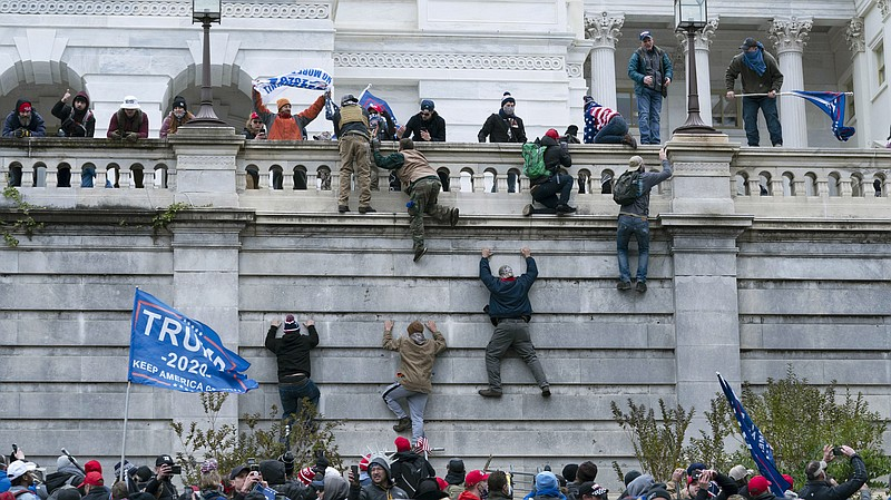 Supporters of President Trump climb the west wall of the U.S. Capitol on Jan....