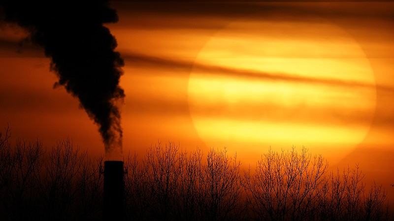 Emissions from a coal-fired power plant are silhouetted against the setting s...