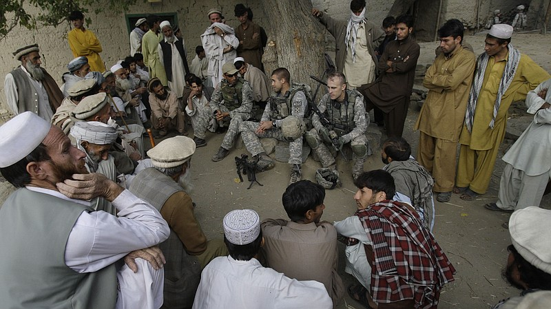 An American lieutenant, center, meets with villagers in Afghanistan's Kunar p...