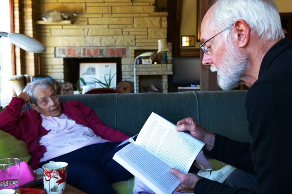 Margaret Zerwekh, who has lived in the mill house for half a century, listens to Milton Bates read from his book,