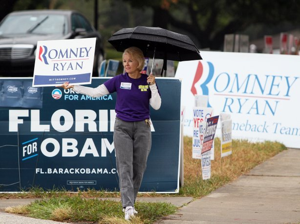 Doran holds a Mitt Romney sign and an umbrella outside Precinct 116, at the Southwest Branch of the Orange County Library in Dr. Phillips area of south Orlando, Florida, Tuesday, Nov. 6.