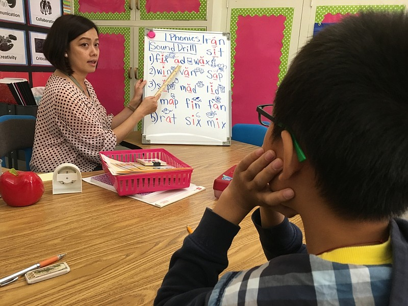 San Gabriel teacher Jenny Tan helps a student who's been in the U.S. less tha...