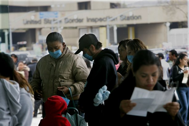 Pedestrians stand in line at the United States-Mexico border while wearing a surgical masks at the Port of Entry on April 27, 2009 in Tijuana, Mexico.