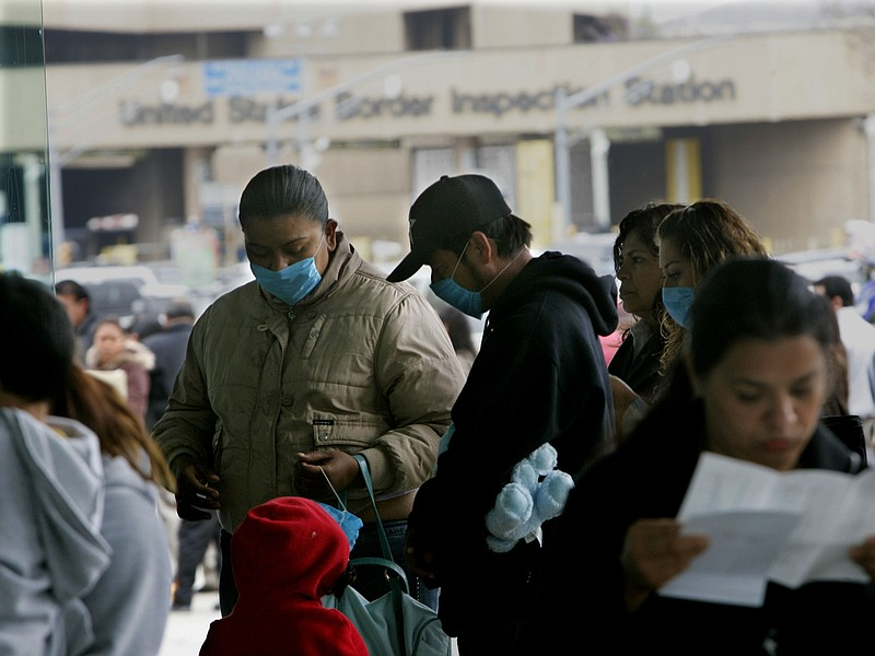 Pedestrians stand in line at the United States-Mexico border while wearing a ...