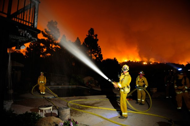 Firefighers spray white foam on a house as flames approach homes in the Jesus...