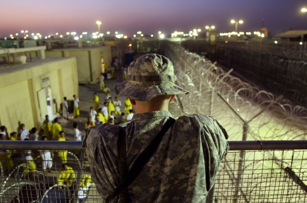 A U.S. Army soldier watches Iraqi detainees at the Camp Cropper detention center September 19, 2007 in Baghdad, Iraq.