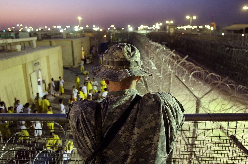A U.S. Army soldier watches Iraqi detainees at the Camp Cropper detention cen...
