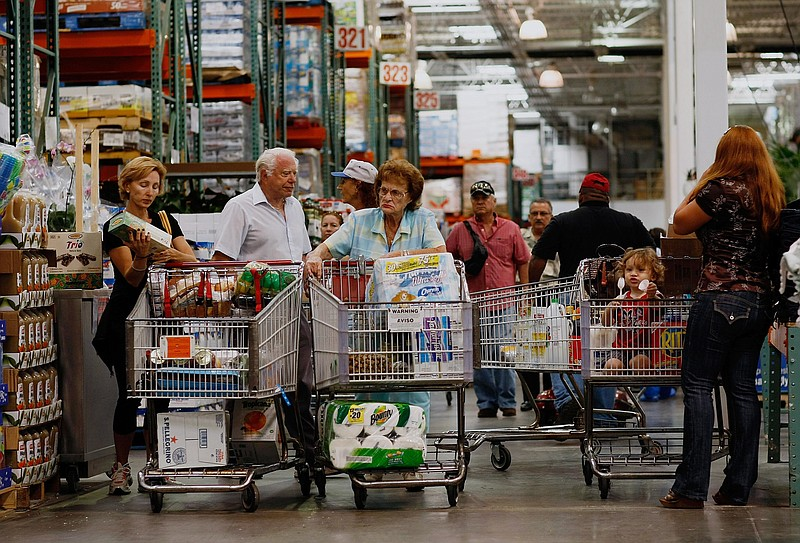 Michael Kaire (2nd L) and Sylvia Kaire (C) and others shop at a Costco store ...
