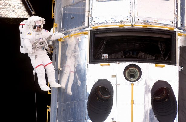 In this handout from NASA, Astronaut John Grunsfeld performs work while parti...