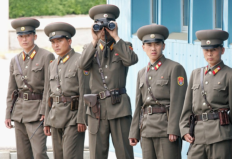 North Korean soldiers look at the south side as Crown Prince Philippe of Belg...