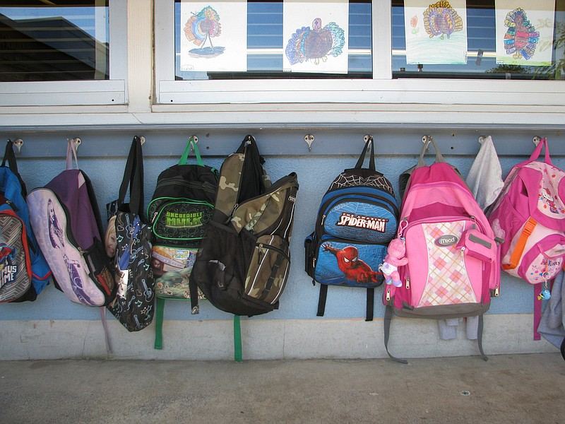 Backpacks hang outside of a San Diego classroom.