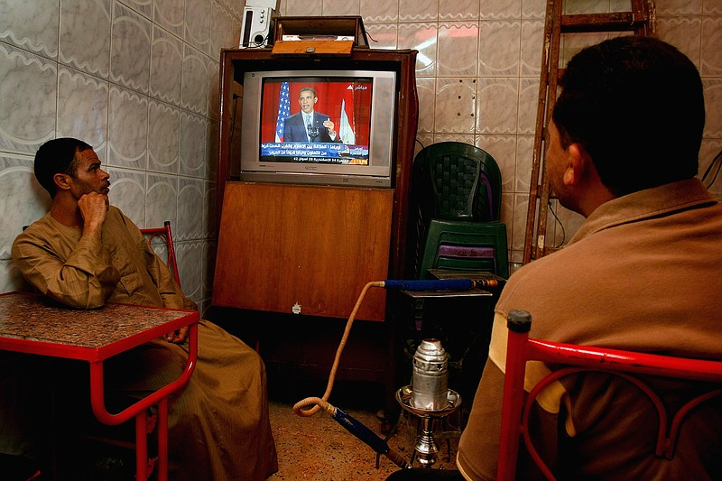 Egyptian men watch US President Barack Obama's key Middle East speech on TV i...