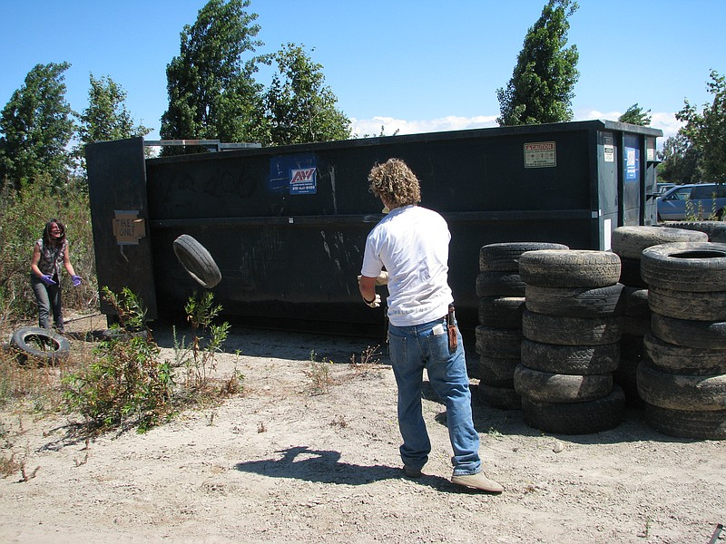 Volunteers work to remove old tires from the Tijuana River Valley during a cl...