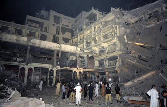 Pakistani police gather beside the destroyed five-star Pearl Continental Hote...