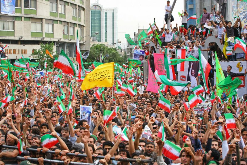Supporters of President Mahmoud Ahmadinejad celebrate during a rally at Valia...