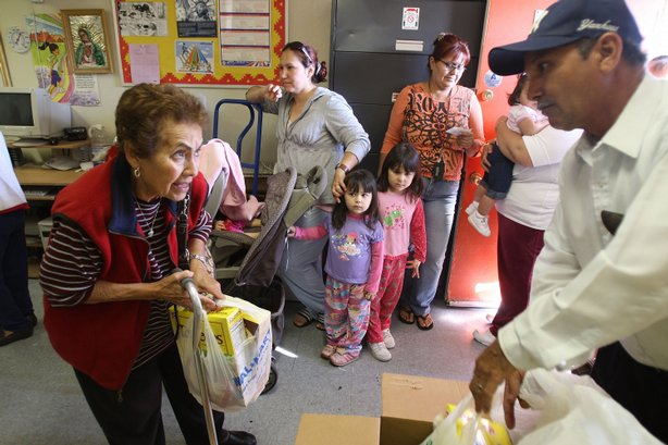 A volunteer gives needy people a monthly food handout from the Imperial Valley Food Bank Bank through the Sister Evelyn Mourey Center on March 13, 2009 in El Centro, California. El Centro is suffering the highest unemployment rate in the nation at 22.6 percent, nearly as high as rates during the Great Depression, with Latinos especially being hit hard.