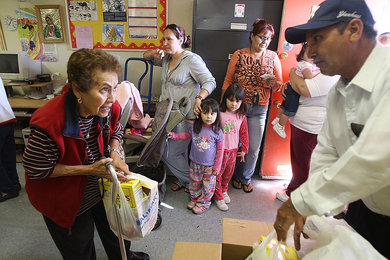 A volunteer gives needy people a monthly food handout from the Imperial Valle...