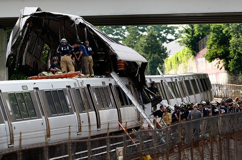 Rescue workers respond to the site of two Metro trains that collided with one...