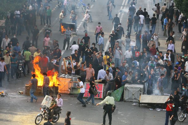 Supporters of Iran's defeated presidential candidate Mir Hossein Mousavi set burning barricades in the streets as they protest during a demonstration.