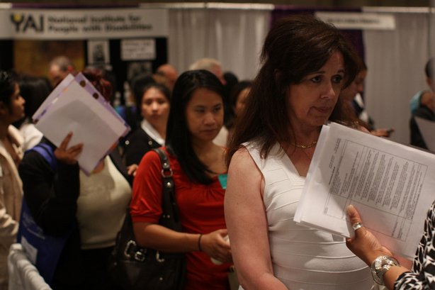 Job seekers wait in line to speak with job recruiters at a job fair for busin...
