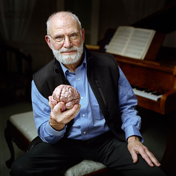Dr. Oliver Sacks sits on a piano bench holding a replica of a human brain. Th...