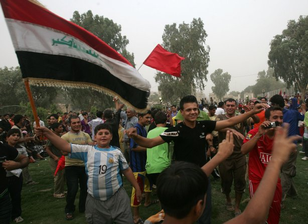 Iraqis wave Iraqi flags and dance as they celebrate the U.S withdrawal from I...