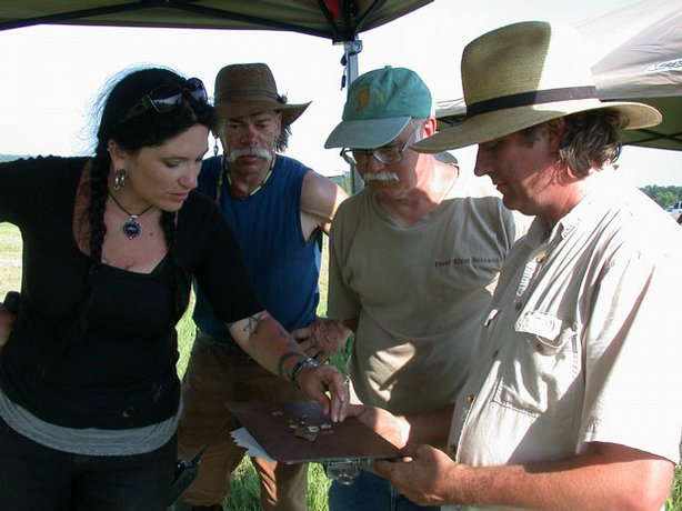<em>TIME TEAM AMERICA</em> digging team members Chelsea Rose and Jeff Brown examine pieces of ceramics with local expert Floyd Mansberger and excavation strategist Eric Deetz. The shards were found at the site of New Philadelphia, Illinois, the first American town founded by a former slave. The ceramics indicate that the team may be digging near the site of an early 19th century home.