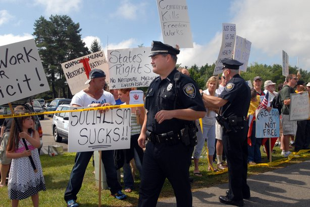 Police stand near protesters outside Portsmouth High School where U.S Preside...