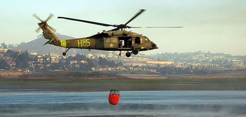 In this photo provided by the U.S. Navy, An MH-60S Seahawk assigned to Helico...