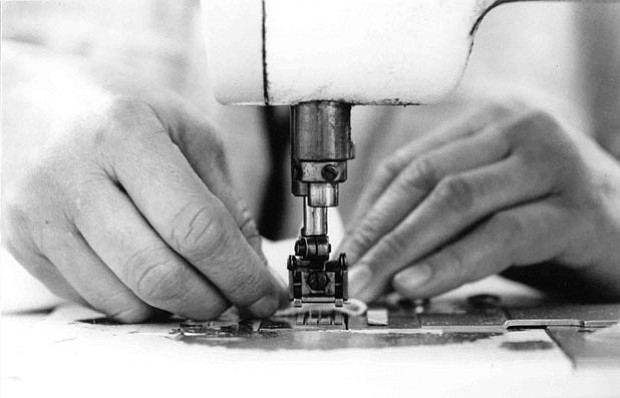 Photo of hands working on a sewing machine.