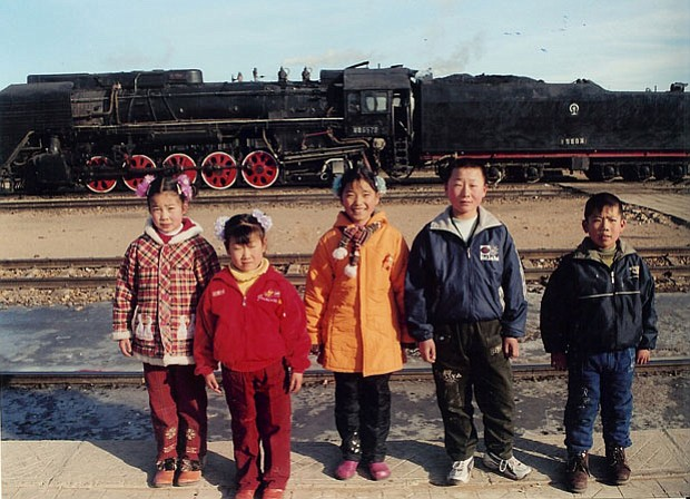Photo of people in China standing in front of train tracks with a train in th...