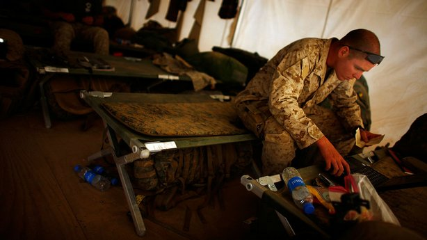 Marine Lt. Samuel Oliver, a platoon leader, sorts through paperwork on his ra...