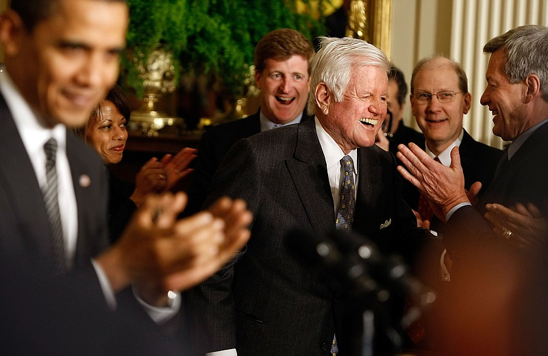 Kennedy receives a standing ovation from President Obama and others as he arr...