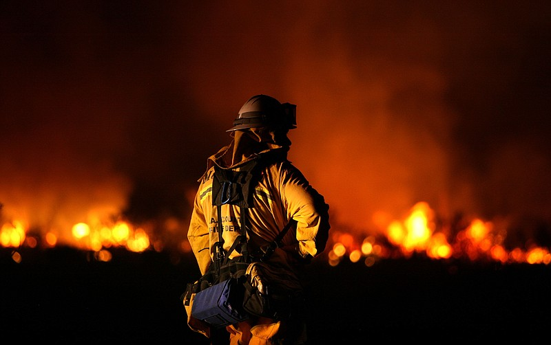 A Los Angeles County fire fighter monitors hot spots as he fights the Station...