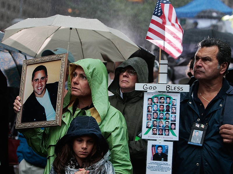 Relatives of victims stand before a ceremony marking the eighth anniversary o...
