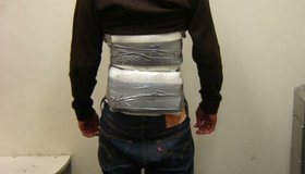 A teen is caught crossing the border with packages of illegal narcotics taped to his body.