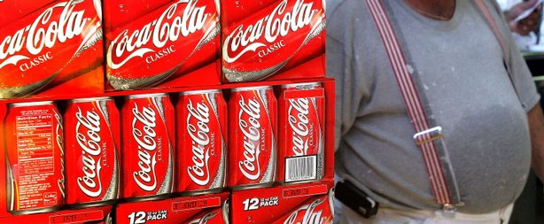A heavyset man passes cartons of Coca-Cola displayed in a grocery store in De...