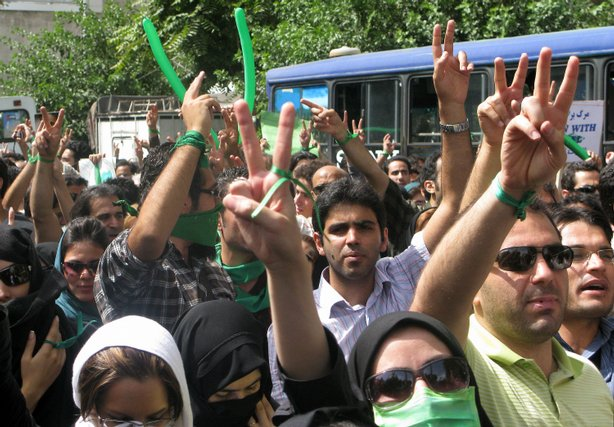 Iranian opposition supporters, wearing green accessories, take part in the Qu...