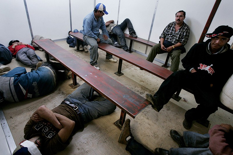 Illegal immigrants sit in a Customs and Border Patrol detention facility afte...