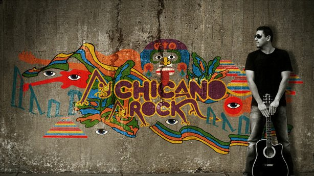 "A man with a guitar standing next to a colorful street mural that reads ""Chicano Rock."" Design by eatdrink and James Adamé."
