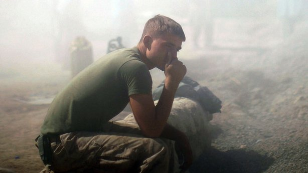 A Marine with Fox Company sits in the dust and mud of the flooded entrance to...
