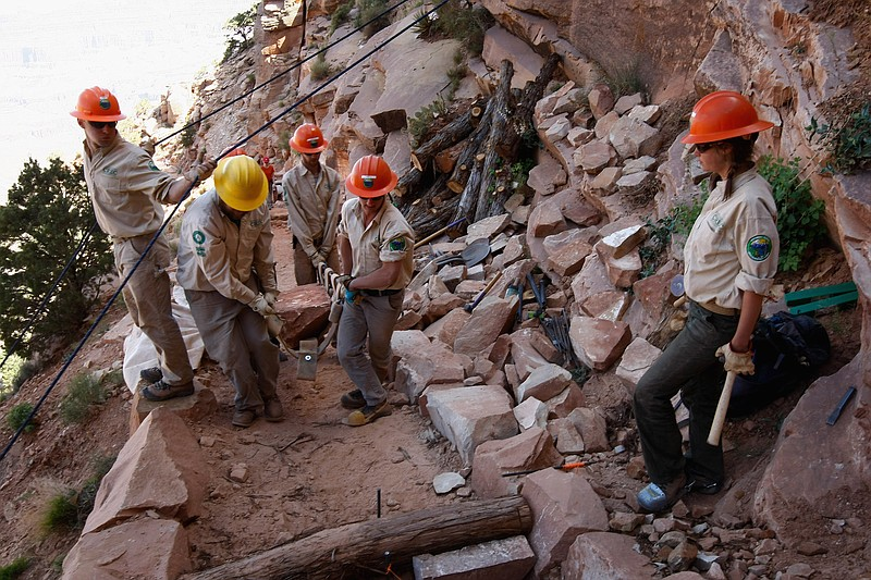 Park workers move a heavy rock while working on a federal stimulus funded tra...
