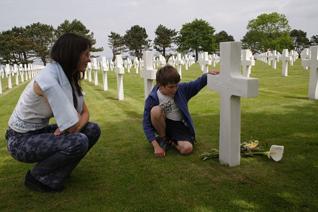 A mother and son visit a grave at Normandy American Cemetery.