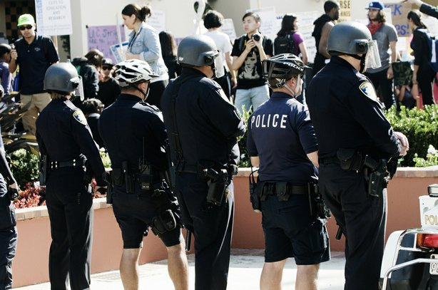 Police stand guard as hundreds of demonstrators outside UCLA's Covel Commons ...